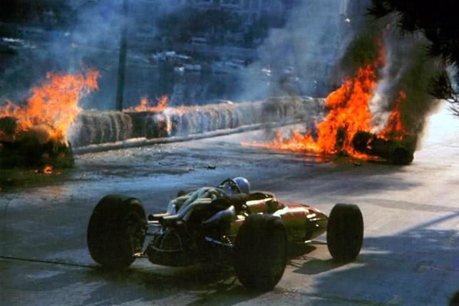 Крис Эймон проезжает мимо горящей машины своего напарника Лоренцо Бандини