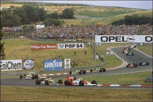 Будущий победитель Гран При Венгрии 1988 года Айртон Сенна лидирует в дебюте гонки. Машину его напарника Алена Проста едва видно