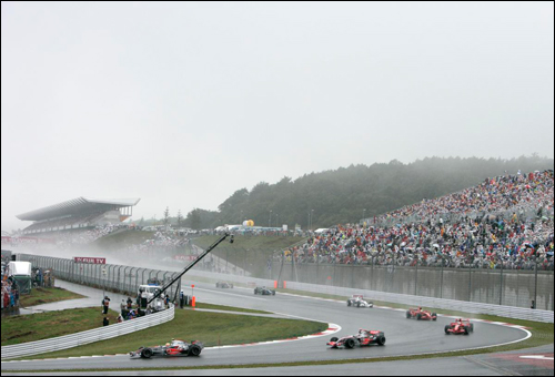 Льюис Хэмилтон лидирует на старте Гран При Японии 2007 года. Пилоты едут за машиной безопасности