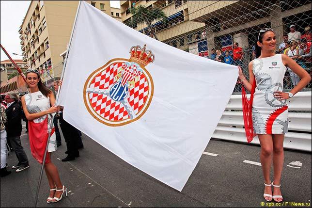 Девушки на стартовом поле с флагом организаторов гонки – автоклуба Монако