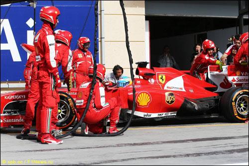 Механики Ferrari пытаются закрыть плоскость заднего крыла после отказа системы DRS на машине Фернандо Алонсо