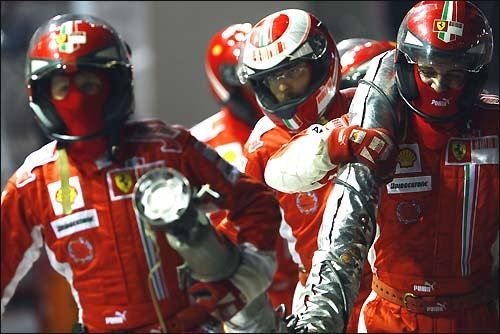 Механики Ferrari возвращают в боксы заправочный шланг, вырванный Фелипе Массой...