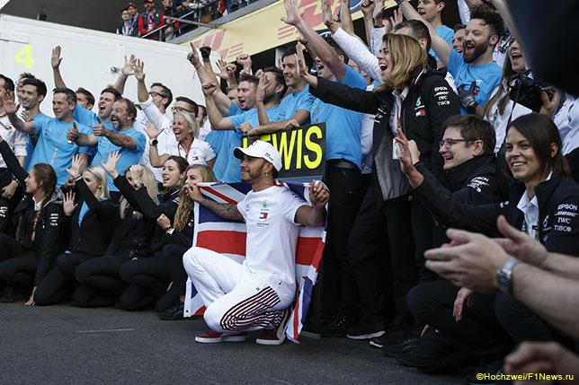 Льюис Хэмилтон празднует вместе с командой победу в чемпионате
