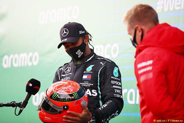 Льюис Хэмилтон принимает от Мика Шумахера шлем, в котором семикраный чемпион мира выступал за Mercedes в 2021 году
