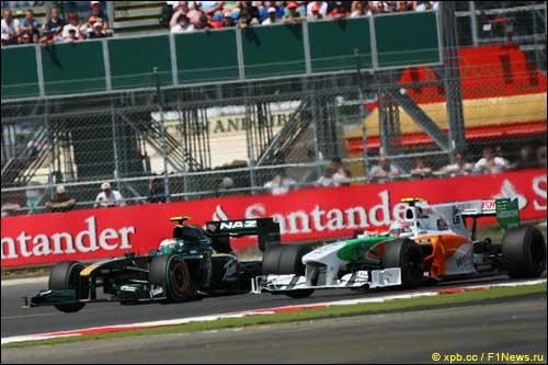 Машины Lotus Racing и Force India на трассе Гран При Великобритании в Сильверстоуне