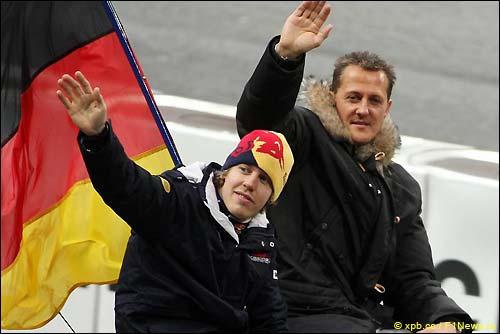Себастьян Феттель и Михаэль Шумахер приветствуют болельщиков перед стартом Гонки Чемпионов