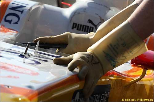 Механик в изолирующих перчатках - на машине установлена KERS
