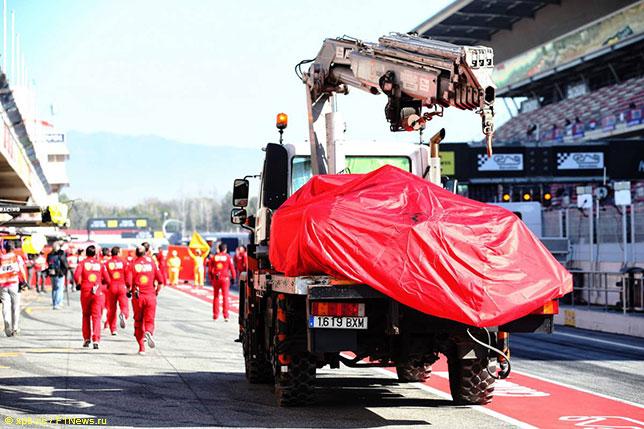 Машину Ferrari возвращают в боксы команды после аварии на тестах в Барселоне