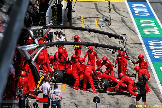 Механики Ferrari закатывают машину Феттеля в боксы